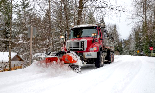 A truck with snowplow clears the road, one of many services provided by public works